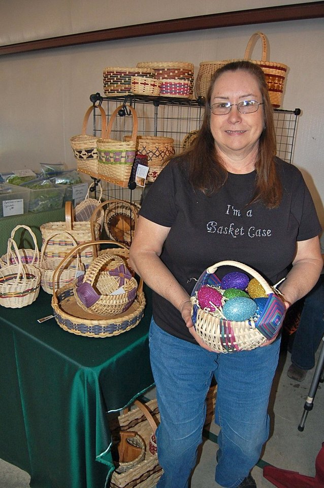 Photo - Pauline Asbury, who has been designing and weaving custom baskets since 1999, stands with some of her creations at her Habasketry booth at the OSU-OKC Farmers Market in Oklahoma City.  Photo by Annette Price, for The Oklahoman.
