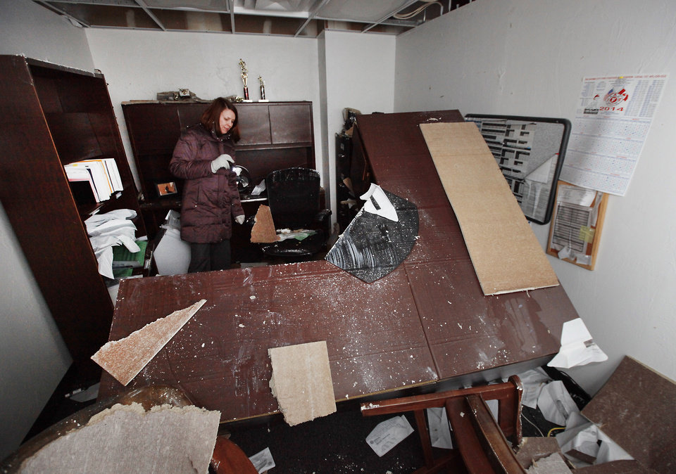 Kristy Yager, Public Information Officer for Oklahoma City, looks through one off the flooded city offices in the basement of the  building at 420 West Main, Monday, February 3, 2014. Photo by David McDaniel, The Oklahoman