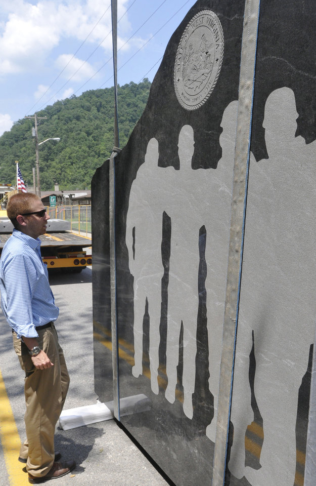 Photo -   Robert Dinsmore Project Designer for Chapman Technical Group gets his first look up close before the granite is lifted into place for a memorial honoring 29 miners killed in the 2010 explosion of the Upper Big Branch mine in Whitesville, W.Va., Tuesday July 17, 2012. Media outlets report that Beckley Crane and Construction Company is expected to complete installation of the six 5-ton slabs on Thursday. Silhouettes of the 29 miners are on one side of the slabs. A history of coal mining in West Virginia is on the other side. (AP Photo/The Charleston Daily Mail, Tom Hindman)