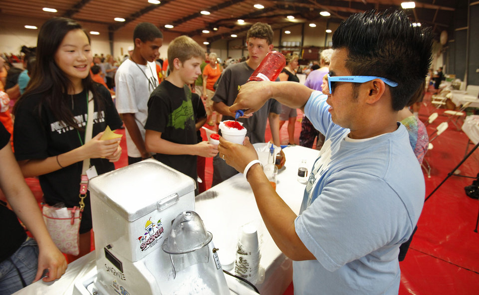 Photo - Eskimo Snow owner Adrian Buendia makes snow cones for the crowd at last year's Taste of Norman event.  THE OKLAHOMAN ARCHIVES