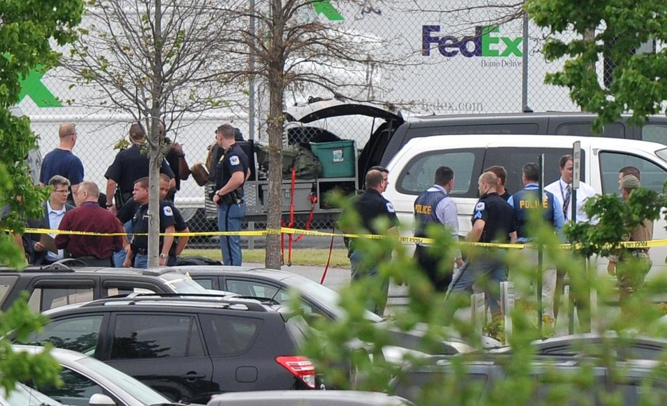 Photo - Police officials rope off the scene of a shooting at a FedEx facility in Kennesaw, Ga., on Tuesday, April 29, 2014.  A shooter described as being armed with an assault rifle and having bullets strapped across his chest