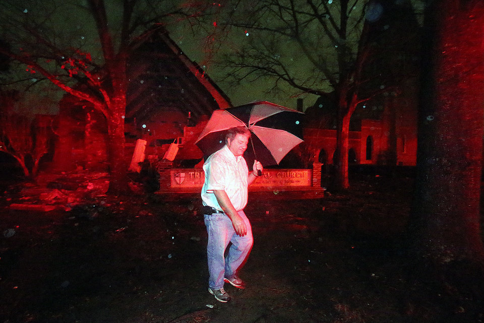 Photo - David Webb walks in front of Trinity Episcopal Church on Dauphin St. in Mobile, Ala. on Christmas Day, Tuesday, Dec. 25, 2012. A tornado hit midtown Mobile causing extensive damage to the church. (AP Photo/AL.com, Bill Starling) MAGS OUT