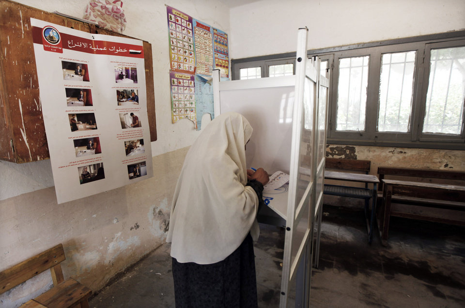 Photo -   An Egyptian woman votes during the first day of the presidential election in a polling station in Alexandria, Egypt, Wednesday, May 23, 2012. Egyptians went to the polls on Wednesday morning to elect a new president after the fall of ex-President Hosni Mubarak last year. (AP Photo/Khalil Hamra)