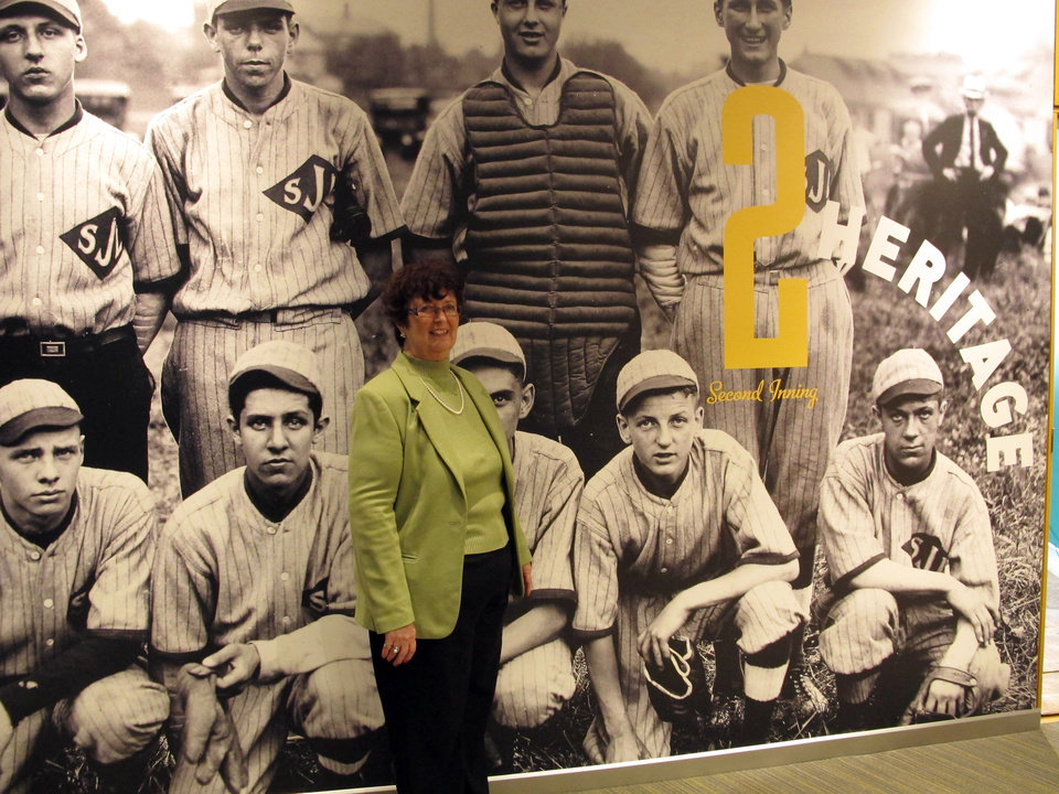 Photo - In this Wednesday, April 24, 2013 photo, Karen Stotz Myers, the daughter of Little League Baseball founder Carl Stotz, poses in front of a picture at a new exhibit at the Little League museum in South Williamsport, Pa. Kneeling on the ground in the image, to Stotz Myers' right, is her father in a picture taken when he was a boy playing for his school team. (AP Photo/Genaro C. Armas)
