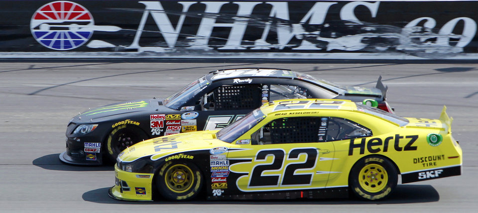 Photo - Brad Keselowski (22) slides down to pass Kyle Busch in turn two during the NASCAR Nationwide Series auto race at New Hampshire Motor Speedway Saturday, July 12, 2014, in Loudon, N.H. Keselowski went on to win the race, Busch came in second. (AP Photo/Jim Cole)