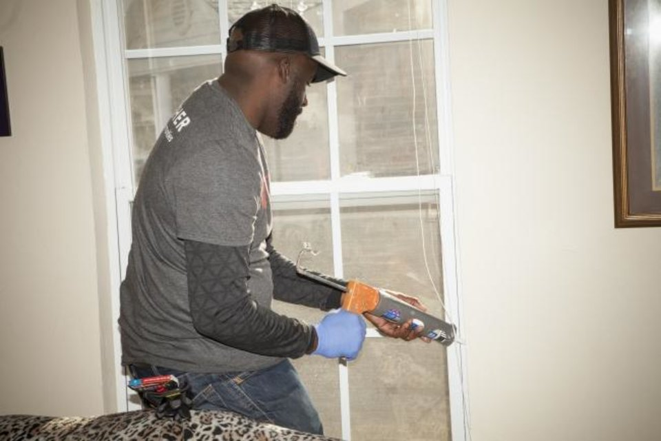 Photo -  Oklahoma Gas and Electric Co. volunteer Johnny Whitfield caulks a window as part of the utility's Silver Energy Sweep program it held in Oklahoma City on Monday and Tuesday.