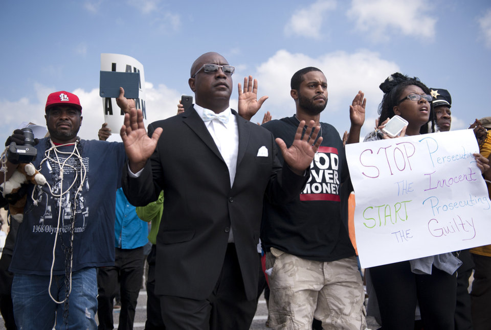 Photo - Protestors march along Florissant Road in downtown Ferguson, Mo. Monday, Aug. 11, 2014. The group marched along the closed street, rallying in front of the town's police headquarters to protest the shooting of 18-year-old Michael Brown by Ferguson police officers on Saturday night. (AP Photo/Sid Hastings)