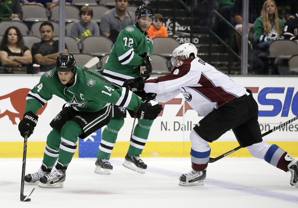 Photo - Dallas Stars left wing Jamie Benn (14) attempts to gain control of the puck under pressure of Colorado Avalanche center Matt Duchene (9) as Stars' Erik Cole (72) watches in the first period of an NHL hockey preseason game on Thursday, Sept. 26, 2013, in Dallas. (AP Photo/Tony Gutierrez)