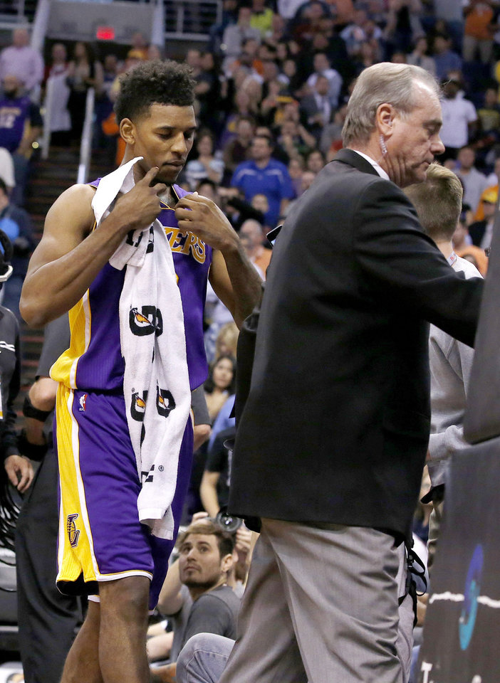 Photo - Los Angeles Lakers' Nick Young, left, is escorted from the court by security after being ejected following a scuffle with the Phoenix Suns during the first half of an NBA basketball game Wednesday, Jan. 15, 2014, in Phoenix. Suns' Alex Len was ejected from the game for a flagrant foul. (AP Photo/Ross D. Franklin)