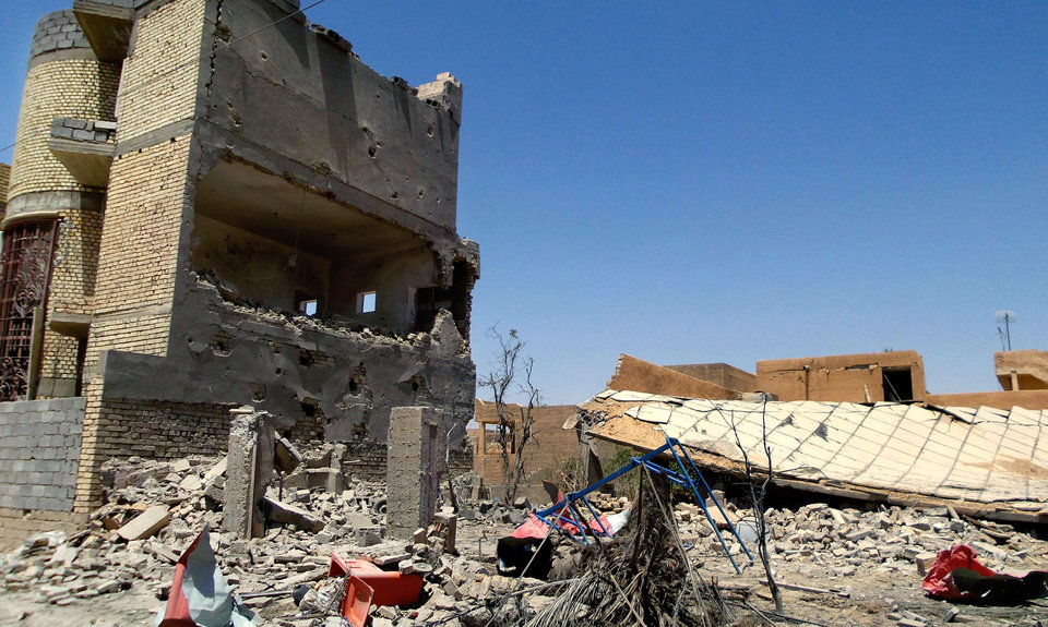 Photo - This photo taken on Tuesday, July 1, 2014, shows damaged homes due to clashes between fighters of the al-Qaida-inspired Islamic State of Iraq and the Levant (ISIL) and Iraqi security forces in Tikrit, 80 miles (130 kilometers) north of Baghdad, Iraq. The Islamic State of Iraq and the Levant announced this week that it has unilaterally established a caliphate in the areas under its control. It declared the group's leader, Abu Bakr al-Baghdadi, the head of its new self-styled state governed by Shariah law and demanded that all Muslims pledge allegiance to him. (AP Photo)