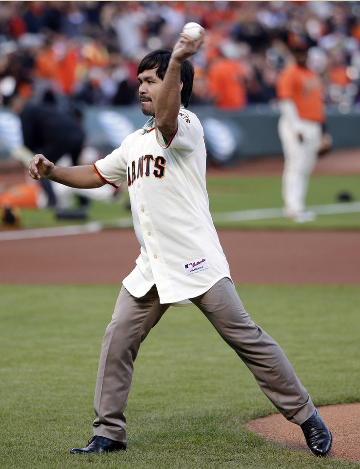 Photo - Boxer Manny Pacquiao throws a ceremonial first pitch before a baseball game between the San Francisco Giants and the Milwaukee Brewers on Friday, Aug. 29, 2014, in San Francisco. (AP Photo/Marcio Jose Sanchez)
