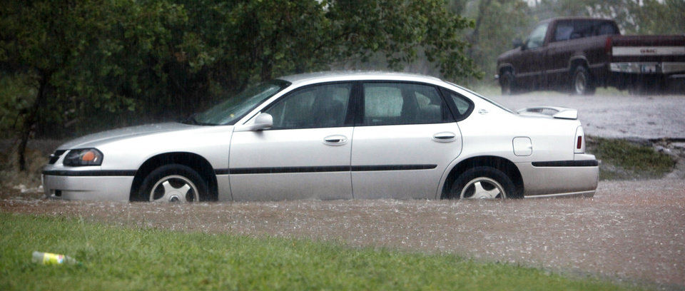 Photo - A car stalled out in high water southbound on Classen just north of Wilshire Blvd. during heavy rains in Oklahoma City Monday, June 14, 2010. Photo by Paul B. Southerland, The Oklahoman
