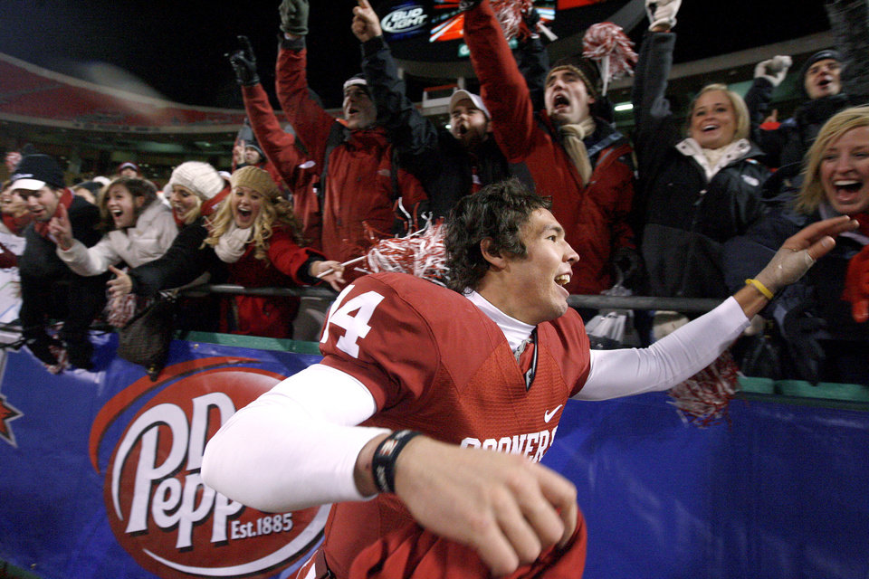 Photo - OU's Sam Bradford celebrates with fans after OU's win in the Big 12 Championship college football game between the University of Oklahoma Sooners (OU) and the University of Missouri Tigers (MU) on Saturday, Dec. 6, 2008, at Arrowhead Stadium in Kansas City, Mo. 