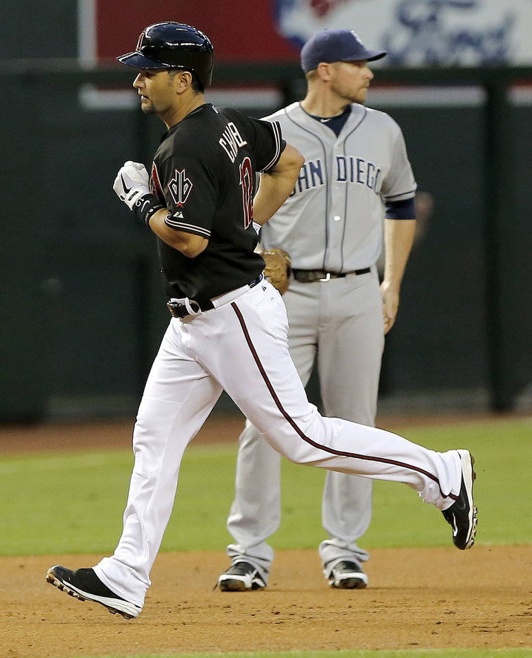 Photo - Arizona Diamondbacks' Eric Chavez, left, rounds the bases after hitting a two-run home run as San Diego Padres' Chase Headley looks away during the first inning of a baseball game on Saturday, May 25, 2013, in Phoenix. (AP Photo/Matt York)