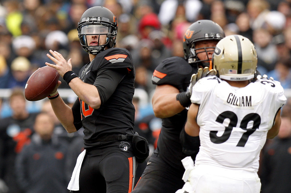 Oklahoma State\'s Clint Chelf (10) drops back to pass during the Heart of Dallas Bowl football game between Oklahoma State University and Purdue University at the Cotton Bowl in Dallas, Tuesday, Jan. 1, 2013. Oklahoma State won 58-14. Photo by Bryan Terry, The Oklahoman