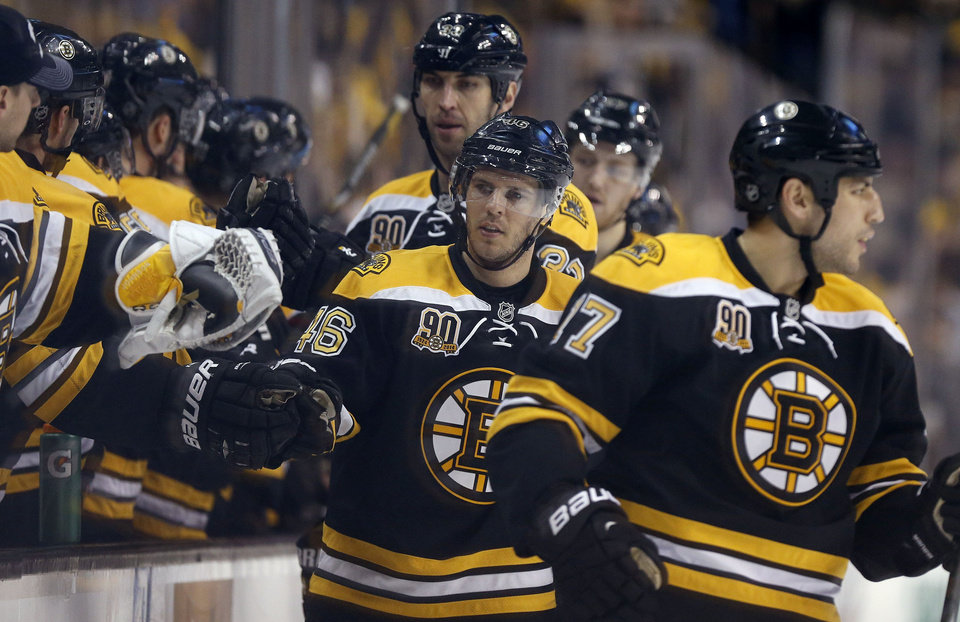 Photo - Boston Bruins' David Krejci (46) celebrates his goal with teammates during the first period of an NHL hockey game against the Buffalo Sabres in Boston, Saturday, April 12, 2014. The Bruins won 4-1. (AP Photo/Michael Dwyer)
