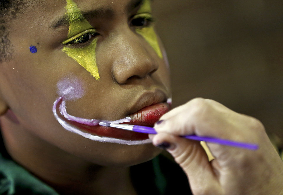 Photo - Paint is applied to Shabarekh Smith's face as he prepares for his role as a clown in a rehearsal of the Circus of the Kids touring performance.