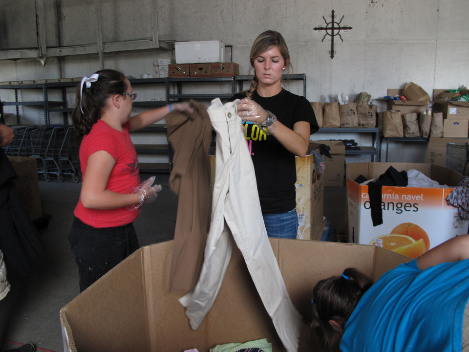 Photo - Jaycee Henson, Braylee Rae Henry's half sister, and Braylee's friend Tiffany Firestone sort clothes in Jesus House.  CARLA HINTON - CARLA HINTON