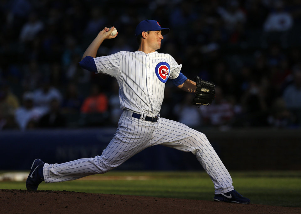 Photo - Chicago Cubs starting pitcher Kyle Hendricks delivers in a setting sun during the first inning of a baseball game against the Milwaukee Brewers Tuesday, Aug. 12, 2014, in Chicago. (AP Photo/Charles Rex Arbogast)