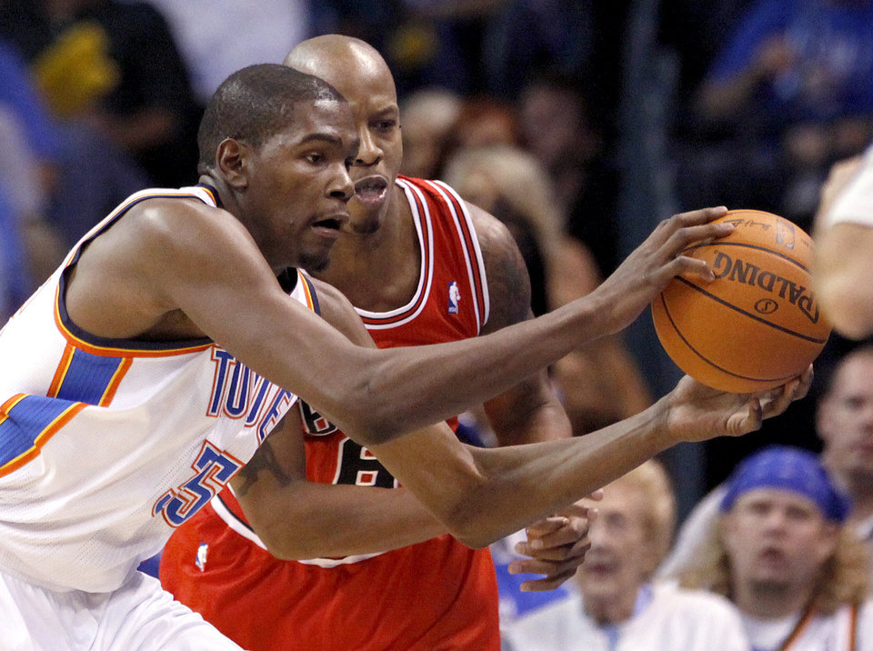 Photo - Oklahoma City's Kevin Durant steals a pass in front of Chicago's Keith Bogans during the NBA season opener basketball game between the Oklahoma City Thunder and the Chicago Bulls in the Oklahoma City Arena on Wednesday, Oct. 27, 2010. Photo by Sarah Phipps, The Oklahoman