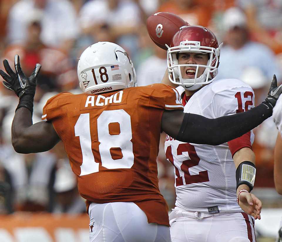 Photo - Oklahoma's Landry Jones (12) is rushed by Texas' Emmanuel Acho (18) on a pass attempt during the Red River Rivalry college football game between the University of Oklahoma Sooners (OU) and the University of Texas Longhorns (UT) at the Cotton Bowl in Dallas, Saturday, Oct. 8, 2011. Photo by Chris Landsberger, The Oklahoman