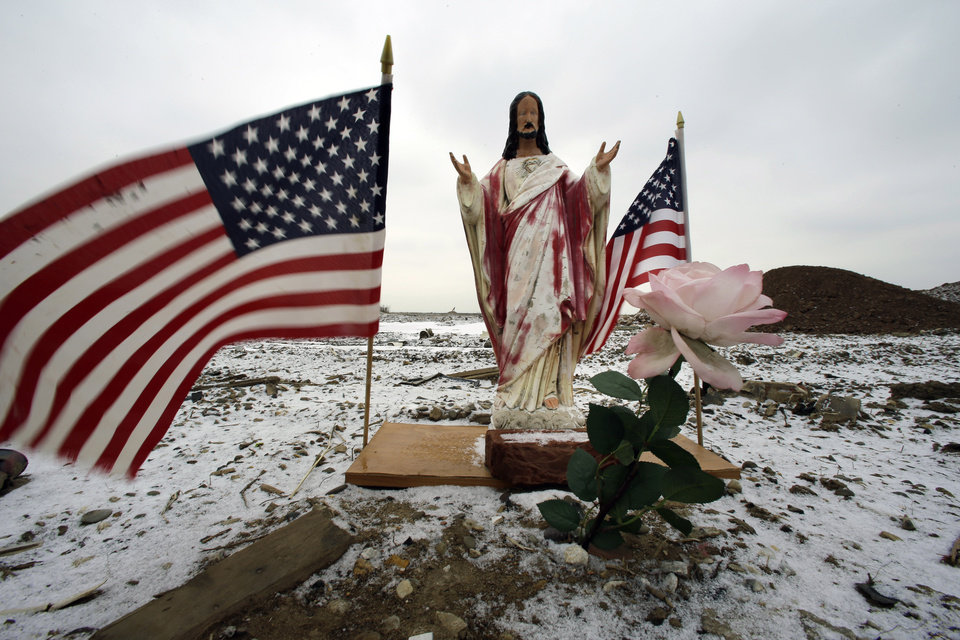 Photo - A religious statue with flags is see Tuesday, Feb. 5, 2013, near empty lots where homes destroyed by Superstorm Sandy were torn down in Union Beach, N.J. New Jersey Gov. Christie told a gathering in Union Beach Tuesday that the National Flood Insurance Program's handling of claims in New Jersey