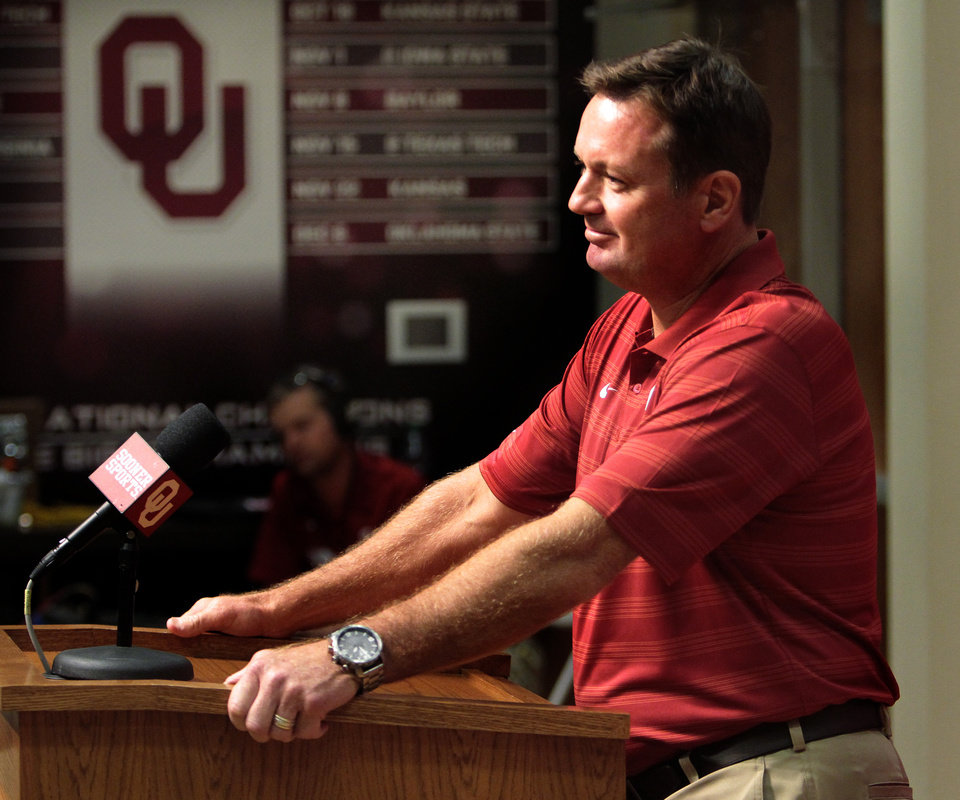 Photo - Head coach Bob Stoops speaks with reporters during the University of Oklahoma (OU)  football team's media day in the Adrian Peterson Team Meeting Room on Saturday, Aug. 2, 2014 in Norman, Okla.  Photo by Steve Sisney, The Oklahoman