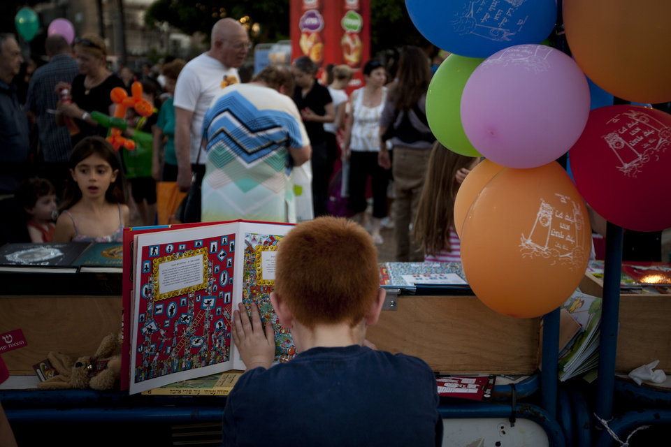 Photo -   In this Wednesday, June 13, 2012 photo, an Israeli boy reads a book behind a counter at the Hebrew Book Week Fair in Tel Aviv. In the land of the People of the Book, the discounted book may soon be a thing of the past. Israeli authors have launched a battle to stop the country's two leading bookstore chains from discounting their works, claiming the price slashing has cut into their royalties. (AP Photo/Ariel Schalit)