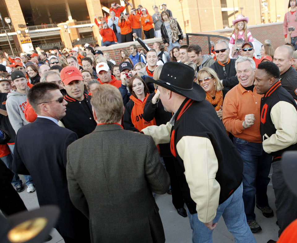 Photo - Garth Brooks, Robin Ventura and Barry Sanders meet with Mike Gundy at the end of the walk to the stadium before the college football game between Oklahoma State University (OSU) and the University of Missouri (MU) at Boone Pickens Stadium in Stillwater, Okla. Saturday, Oct. 17, 2009.  Photo by Doug Hoke, The Oklahoman