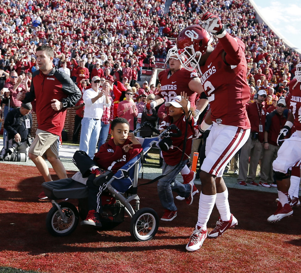 Photo - Titus and Tobias Tate lead the team onto the field before the college football game between the University of Oklahoma Sooners (OU) and the Iowa State University Cyclones (ISU) at Gaylord Family-Oklahoma Memorial Stadium in Norman, Okla. on Saturday, Nov. 16, 2013. Photo by Steve Sisney, The Oklahoman