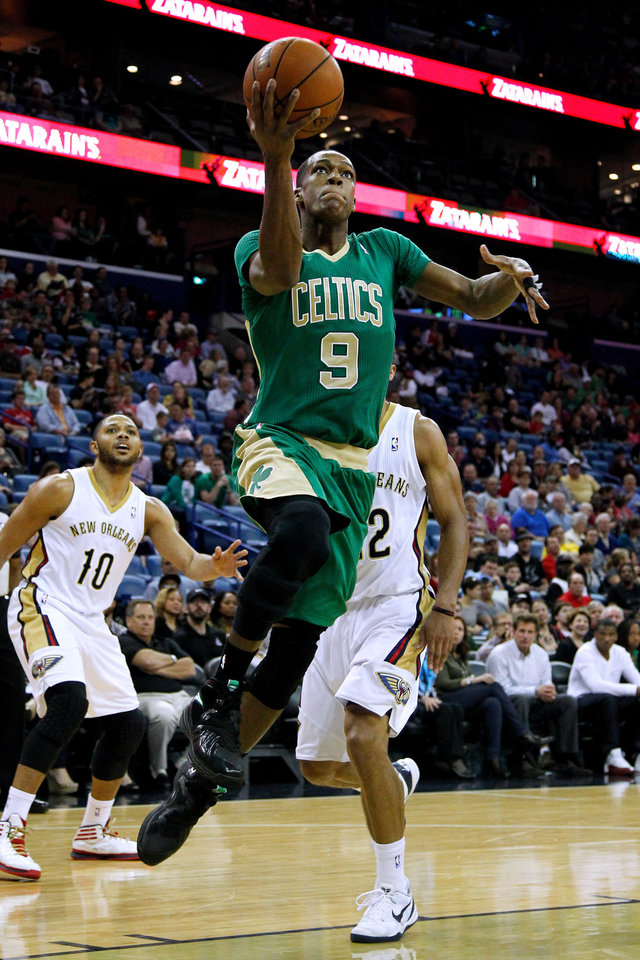 Photo - Boston Celtics guard Rajon Rondo (9) drives to the basket against New Orleans Pelicans guard Eric Gordon (10) and New Orleans Pelicans guard Brian Roberts, right, during the first half of an NBA basketball game in New Orleans, Sunday, March 16, 2014. (AP Photo/Jonathan Bachman)