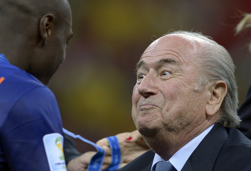 Photo - FIFA President Sepp Blatter, right, presents Netherlands' Bruno Martins Indi with his 3rd place medal after the World Cup third-place soccer match between Brazil and the Netherlands at the Estadio Nacional in Brasilia, Brazil, Saturday, July 12, 2014. The Netherlands won the match 3-0.    (AP Photo/Manu Fernandez)