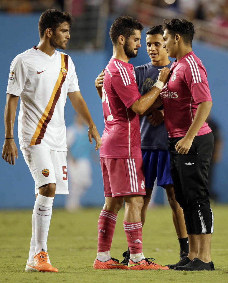Photo - Roma's Leandro Castan, left, watches as Real Madrid's Isco, center, autographs the jersey of a fan late in the second half of a Guinness International Champions Cup soccer tournament match against Roma, Tuesday, July 29, 2014, in Dallas. Several fans made it onto the field, some able to acquire autographs and selfies from players, in the 1-0 Roma win. (AP Photo/Tony Gutierrez)