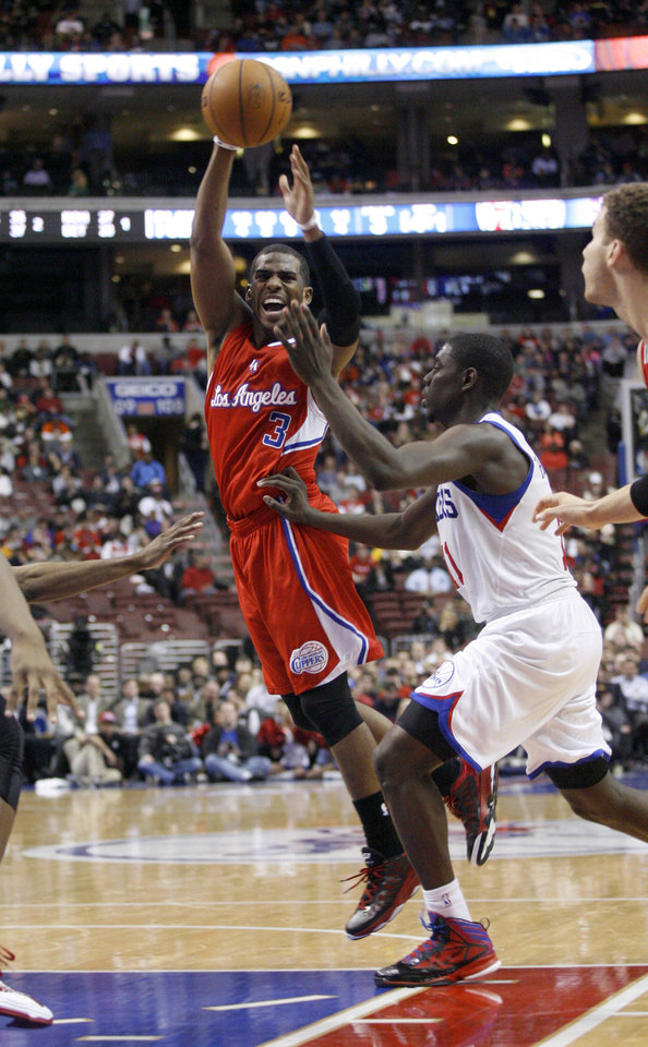 Photo - Los Angeles Clippers' Chris Paul (3) looks to pass as Philadelphia 76ers' Jrue Holiday, right, defends in the first half of an NBA basketball game, Monday, Feb. 11, 2013, in Philadelphia. (AP Photo/H. Rumph Jr)