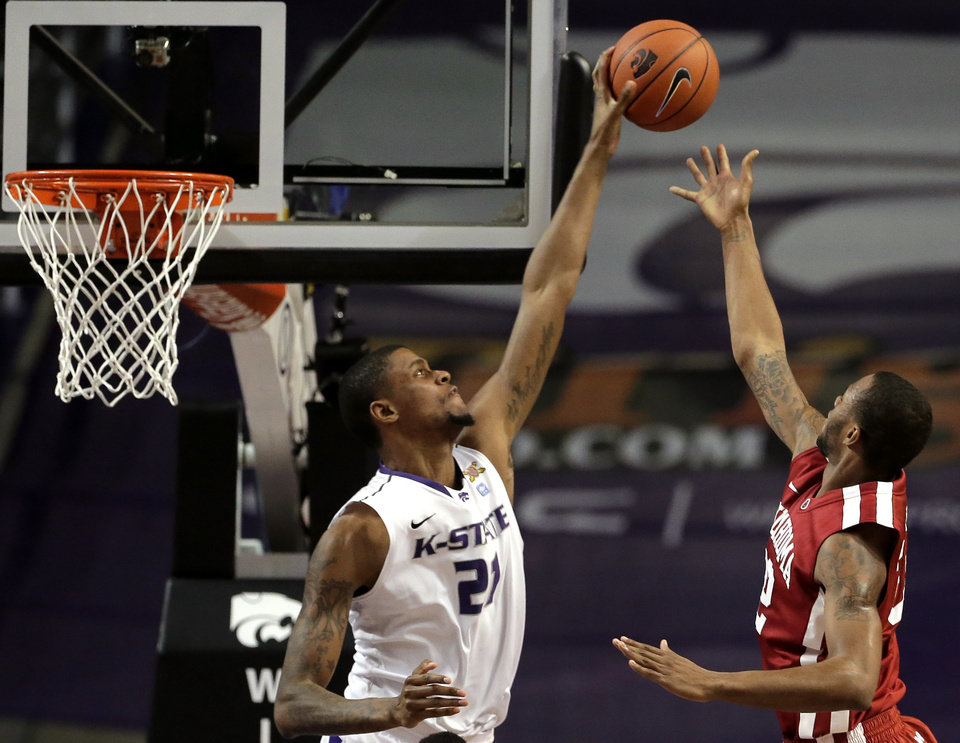 Photo - Kansas State forward Jordan Henriquez, left, blocks a shot by Oklahoma forward Amath M'Baye (22) during the second half of an NCAA college basketball game Saturday, Jan. 19, 2013, in Manhattan, Kan. Kansas State won the game 69-60. (AP Photo/Charlie Riedel) ORG XMIT: KSCR108