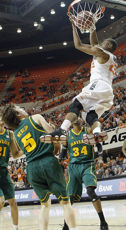 Photo - Oklahoma State 's Markel Brown (22) dunks the ball over Baylor's Brady Heslip (5) and Cory Jefferson (34) during the college basketball game between the Oklahoma State University Cowboys (OSU) and the Baylor University Bears (BU) at Gallagher-Iba Arena on Wednesday, Feb. 5, 2013, in Stillwater, Okla. Photo by Chris Landsberger, The Oklahoman