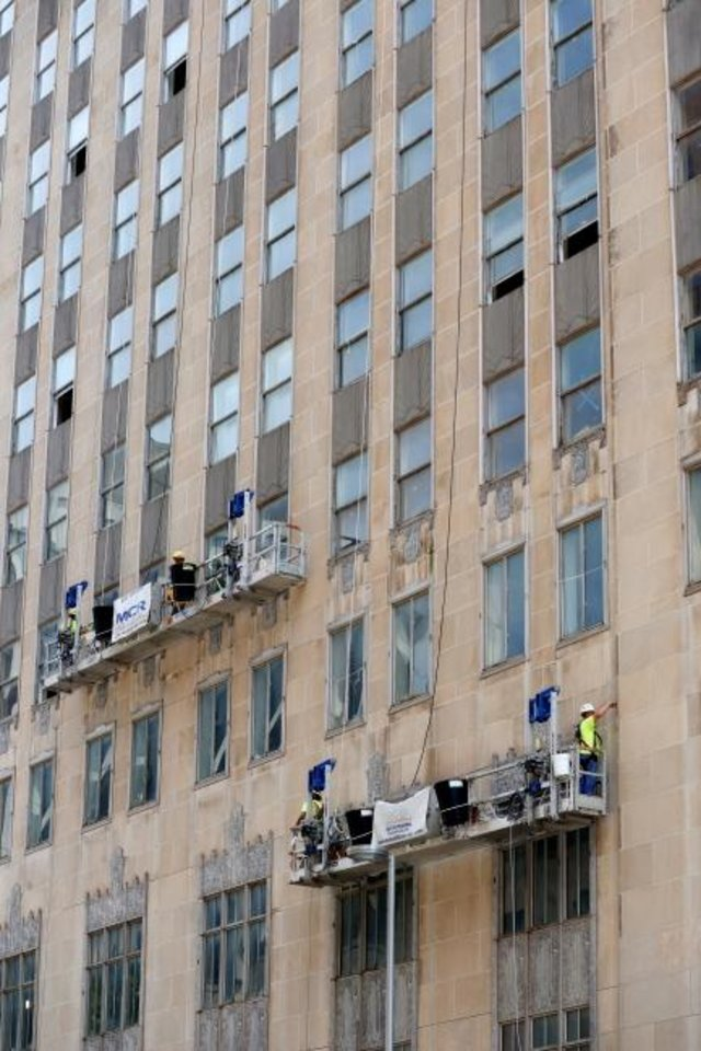 Photo -  Work has moved to the north exterior of the First National Center as crews scale the 33-story tower securing limestone panels that were in danger of falling off as some did at the start of the  $283 million redevelopment. [DOUG HOKE/THE OKLAHOMAN]