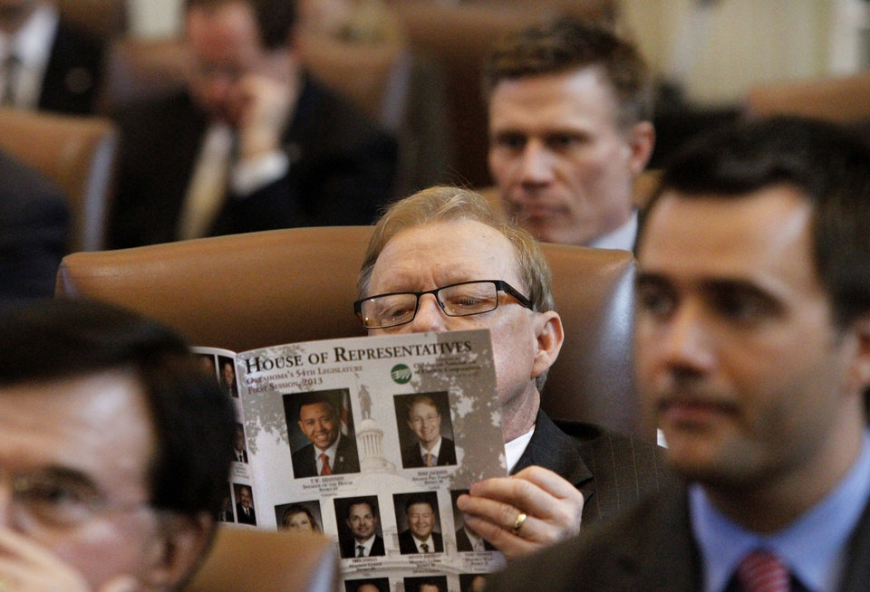 Photo - Rep. Earl Sears, R-Bartlesville, looks at a current legislative directory as he waits for the governor to arrive to deliver her speech. Oklahoma Gov. Mary Fallin delivers her State of the State address to lawmakers Monday afternoon, Feb. 4, 2013, in the House of Representatives chamber. Also attending were members of the governor's cabinet and members of the judiciary.   Photo by Jim Beckel, The Oklahoman