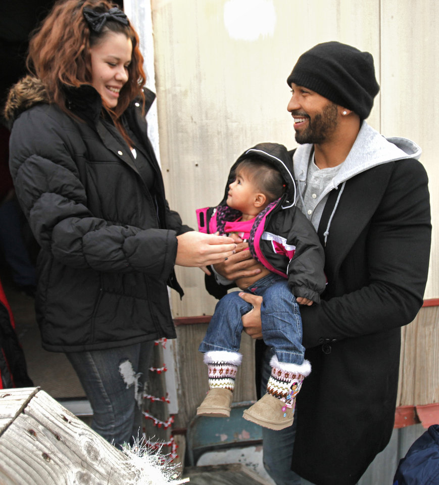 CHILD / CHILDREN / KIDS / CHRISTMAS / HOLIDAY / GIFTS: Baseball superstar Matt Kemp hands Ara Gonzalez, 16 months, back to her mother Breanna Aguilar, 17, on Thursday, Dec. 22, 2011, in Midwest City, Okla. Both are wearing new coats provided by Kemp.  Photo by Steve Sisney, The Oklahoman