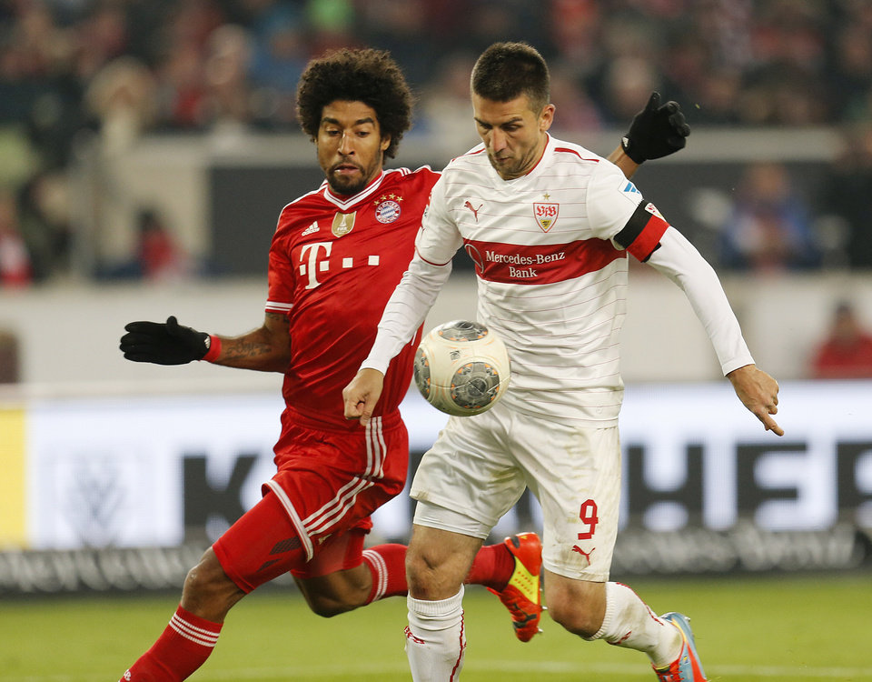 Photo - Stuttgart's Vedad Ibisevic of Bosnia, right, and Bayern's Dante of Brazil challenge for the ball during a German first soccer division Bundesliga match between VfB Stuttgart and FC Bayern Munich in Stuttgart, Germany, Wednesday, Jan. 29, 2014. (AP Photo/Michael Probst)