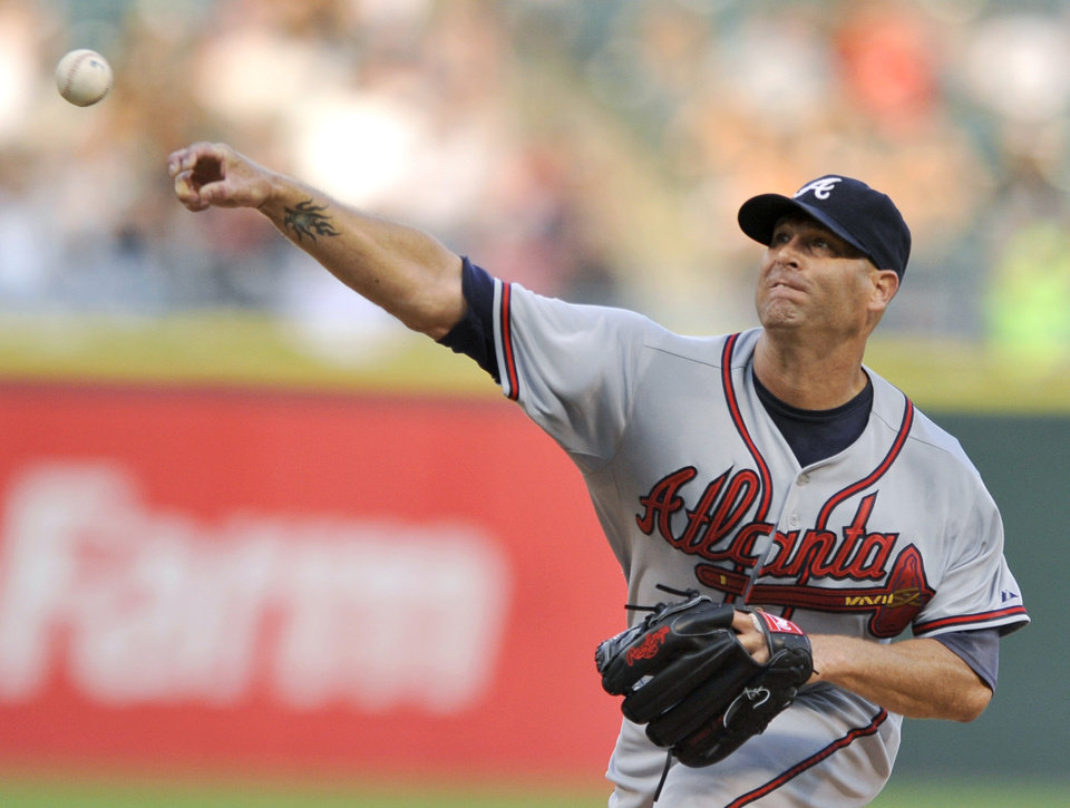 Photo - Atlanta Braves starter Tim Hudson delivers a pitch during the first inning of a baseball game against the Chicago White Sox in Chicago, Friday, July 19, 2013. (AP Photo/Paul Beaty)