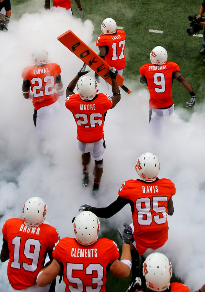 Photo - Quinton Moore (26) carries the BIG STICK on to the field before the Oklahoma State University (OSU) college football game with the University of Houston (UH) at Boone Pickens Stadium Saturday, Sept. 6, 2008 in Stillwater, Okla. BY MATT STRASEN, THE OKLAHOMAN. ORG XMIT: KOD