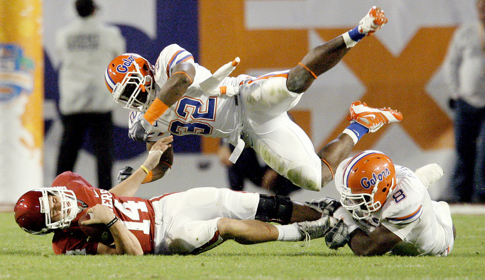 Photo - OU's Sam Bradford gets hit by Florida's Dustin Doe, center, and Carlos Dunlap during the second half of the BCS National Championship college football game between the University of Oklahoma Sooners (OU) and the University of Florida Gators (UF) on Thursday, Jan. 8, 2009, at Dolphin Stadium in Miami Gardens, Fla. 