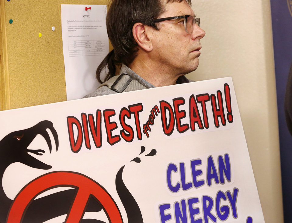 Photo -  A protester holds a sign Monday at a news conference against the construction of Diamond Pipeline which is scheduled to run through Oklahoma.  [Photo by Jim Beckel, The Oklahoman]