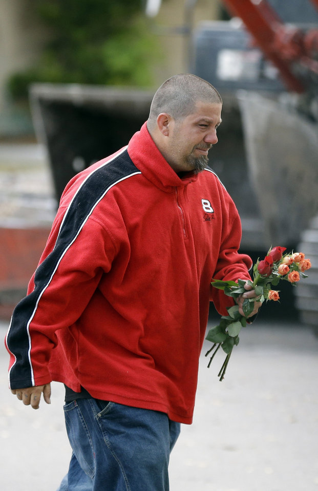 Jeremy Bush carries flowers to a home over a huge sinkhole that swallowed his brother Jeffrey late Thursday in Seffner, Fla., Sunday, March 3, 2013. Crews are set to begin the demolition of the Florida home on Sunday, after search personnel failed to find Jeffrey Bush. (AP Photo/Chris O'Meara)