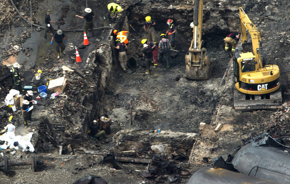 Photo - This aerial photo, workers comb through the debris after a train derailed causing explosions of railway cars carrying crude oil Tuesday, July 9, 2013 in Lac-Megantic, Quebec, Canada on Tuesday July 9, 2013.  At least thirteen people were confirmed dead and nearly 40 others were still missing in a catastrophe that raised questions about the safety of transporting oil by rail instead of pipeline.  (AP Photo/ The Canadian Press, Paul Chiasson)