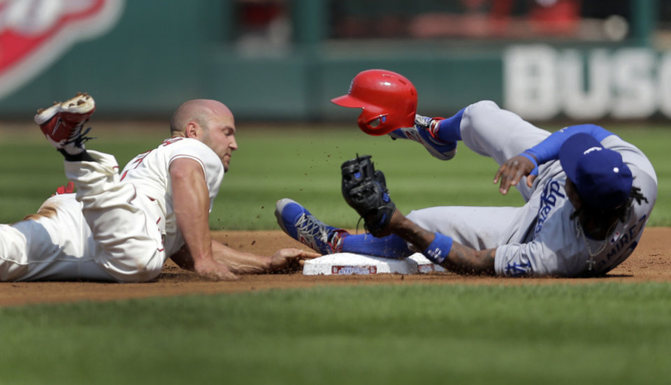Photo - St. Louis Cardinals' Matt Holliday, left, gets back to second on a failed pickoff attempt as Los Angeles Dodgers shortstop Hanley Ramirez covers during the first inning of a baseball game Saturday, July 19, 2014, in St. Louis. (AP Photo/Jeff Roberson)