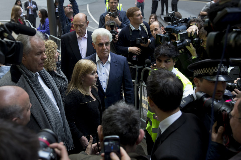 Photo - British public relations guru Max Clifford, center, flanked by his daughter Louise Clifford pauses to pose for members of the media as he leaves his trial at Southwark Crown Court in London, Monday, April 28, 2014.  Leading British public relations agent Clifford on Monday was found guilty of eight counts of indecent assault.  (AP Photo/Matt Dunham)