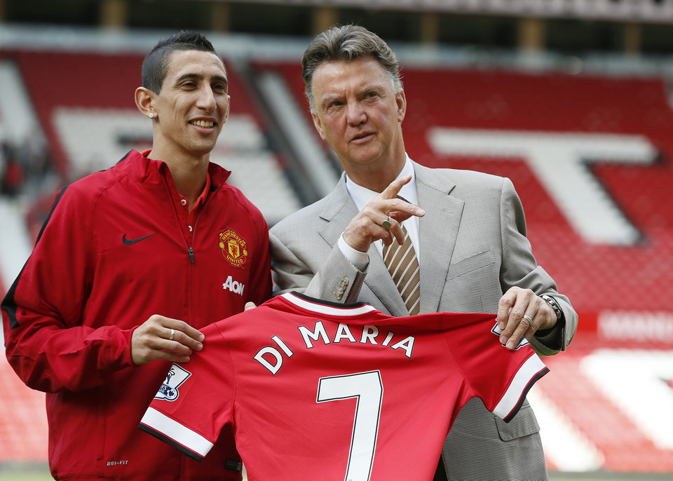 Photo - Manchester United's new player Angel Di Maria left, and manager Louis van Gaal, pose for photographers holding his new shirt, at Old Trafford Stadium in Manchester, England, Thursday, Aug. 28, 2014. Manchester United have signed winger Angel Di Maria from Real Madrid for a British record transfer fee of £59.7m. The Argentine winger had a medical in Manchester on Tuesday and has signed a five-year deal. (AP Photo/Alastair Grant)