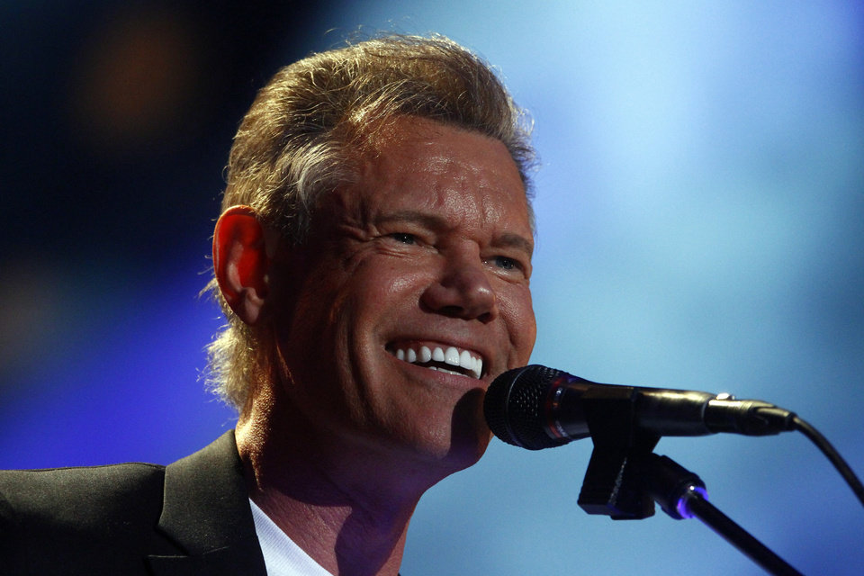 Photo - FILE - In this June 7, 2013 file photo, Randy Travis performs on day 2 of the 2013 CMA Music festival at the LP Field in Nashville, Tenn. Publicist Kirt Webster on Wednesday night, July 10, 2013 said that the 54-year-old Travis is in surgery after suffering a stroke while he was being treated for congestive heart failure because of a viral illness. (Photo by Wade Payne/Invision/AP, File)